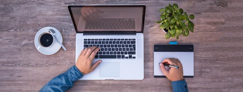 Foto: linke Hand liegt auf Laptop, rechte Hand hält Stift auf einem Grafiktablett