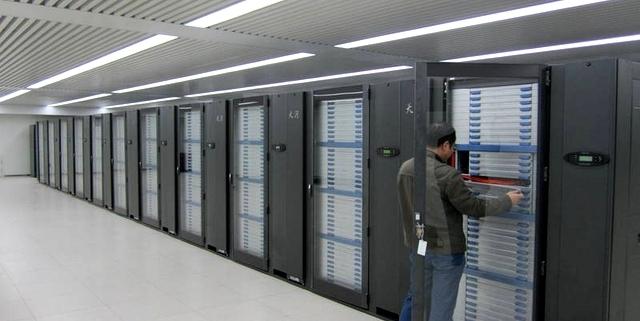 Foto: Mann steht vor einem geöffneten übermannshohem Großrechner neben weiteren Großrechnern