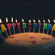 Foto: kleiner Torte mit brennenden Kerzenbuchstaben die die Worte Happy Birthday bilden