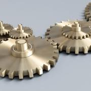 3D-Grafik: mehrere ineinander verzahnte Zahnräder liegen auf hellgrauer Fläche