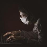 Foto: junger Mann mit Mund-Nasen-Schutz kauert mit seinen Händen auf der Tastatur im dunkeln vor seinem Laptop