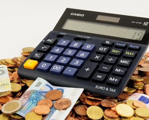 Foto: Taschenrechner liegt auf Hartgeld und einigen Geldscheinen