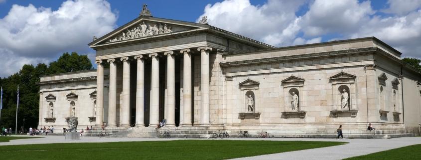 Foto: Gebäude in antikem Stil mit 8 großen Säulen vor dem Eingang und jeweils rechts und links davon mit sich in Nischen befindenden Skulpturen