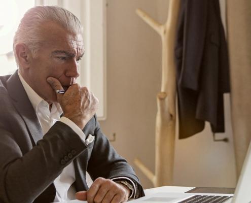 Foto: älterer Mann im Anzug sitzt am Tisch vor einem Laptop