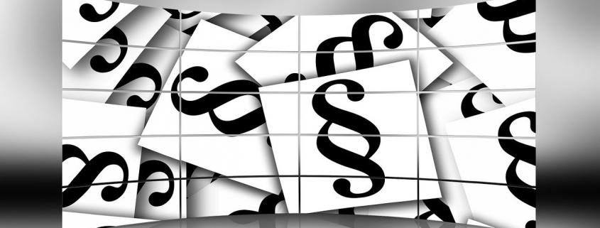 Grafik: mehrere übereinander liegende weiße Karten mit einem Paragraphen-Zeichen darauf