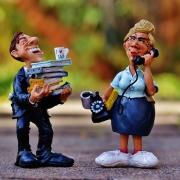 Foto: 2 Plastik-Figuren - lachender Mann mit Heftern auf beiden Unterarmen und telefonierende Frau mit altem Telefon