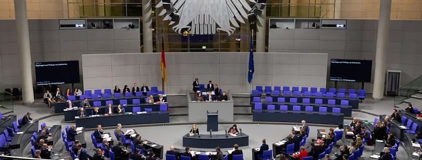 Foto: Sitzreihen im Halbkreis vor und hinter einem Rednerpult. Darüber thront der Bundesadler im Hintergrund