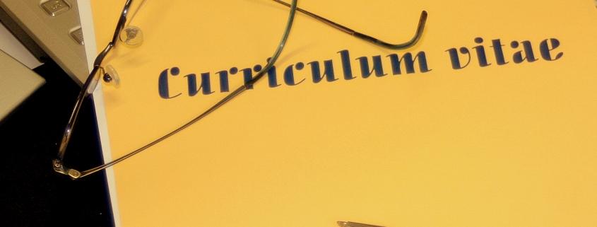 Foto: gelbe Lebenslauf-Mappe mit Brille und Kugelschreiber auf eine Tastatur