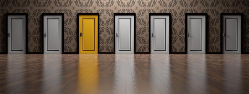 Foto: Sieben sich im Parkett spiegelnde Türen, davon eine gelb.
