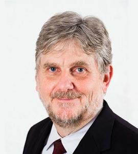 Foto, Portrait: lächelnder Mann mit kurzem Bart im Anzug mit Schlips vor weißem Hintergrund