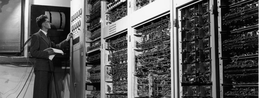Foto - schwarz-weiß: Mann steht vor einem der Ersten Zuse-Computerschränken mit div. Relais aus den 1990er Jahren