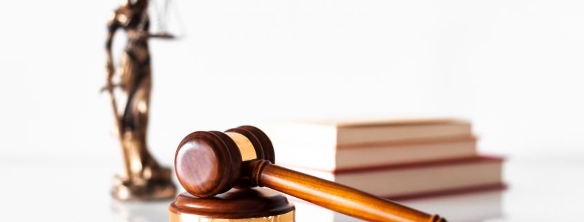 Foto: Richterhammer und drei Bücher sowie eine Justitia-Figur im Hintergrund