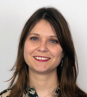 Foto, Porträt: lächelnde Frau mit langen braunen Haaren, roten Lippen und Ohrring am rechten Ohr