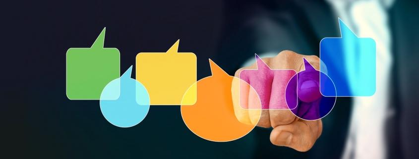 Fotomontage: Finger hinter unterschiedlich farbigen Sprechblasen